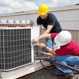 2 mechanical contractors repairing a commercial HVAC system in New Brighton, PA